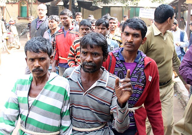 The dozen men were tied together with ropes as they were taken to a police station