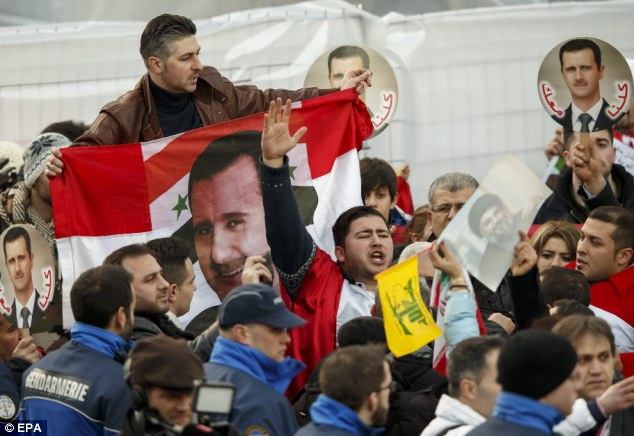 Pro-government: Supporters of Syrian President Bashar al-Assad outside the opening of the Geneva II peace talks, in Montreux, Switzerland yesterday