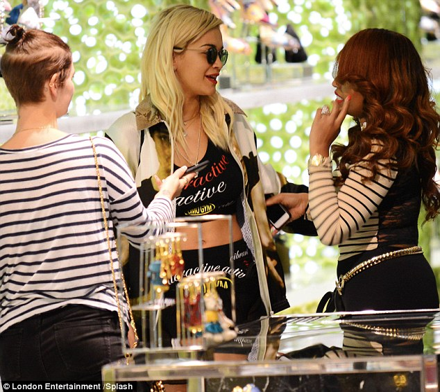 Well-recognised: Singer Rita Ora and her friend Pixie Geldof take time to pose with a fan and check out some perfumes as they shop at Prada