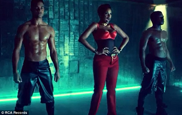 Nice company: The singer croons her lyrics alongside muscly male dancers