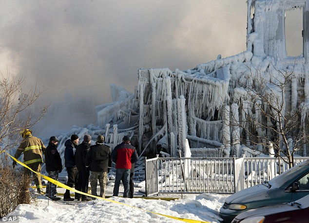 Investigation: Investigator and firefighters survey the damage after the fatal fire