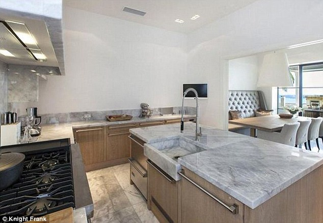 Light: The spacious kitchen features very high ceilings and sleek grey marble countertops. It opens up onto the dining room - an airy space with a wooden dining table surrounded by six armchairs
