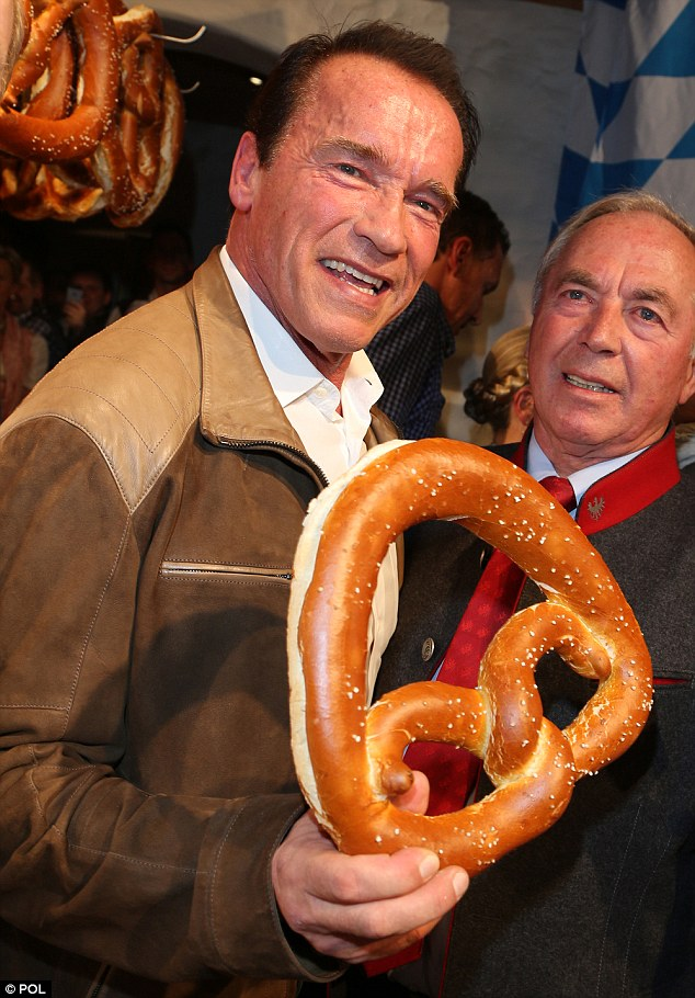 A real mouthful: Schwarzenegger, 66, tackles a giant pretzel at the Hotel Stanglwirt in Kitzbühel, Austria today, at the White Sausage Party