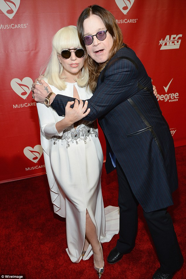 Cuddles with pals: Gaga shared a hug with Ozzy Osbourne who also characteristically opted for tinted glasses at the well-lit event