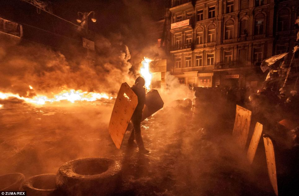 A city in flames: The president's announcement came as fresh violence erupted in Kiev, with a large crowd attacking a government exposition and conference hall
