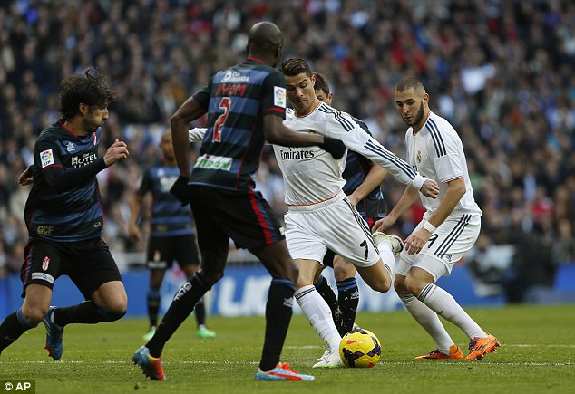 Overcrowded: Ronaldo (C) is surrounded by Granada players before scoring his 22nd league goal of the season