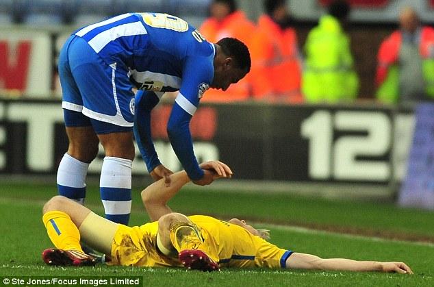 Concerned: Wigan striker Nicky Maynard checks on Parr following Callum McManaman's challenge