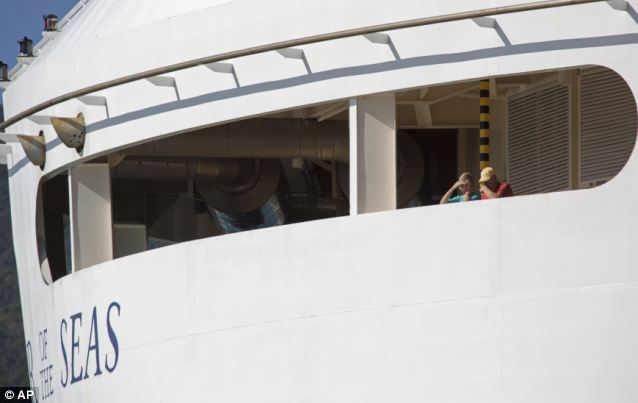 Passengers look out from the Explorer of the Seas as they wait for health officials to conduct their investigation. The number of those who fell ill was past 600, as opposed to the 300 previously thought