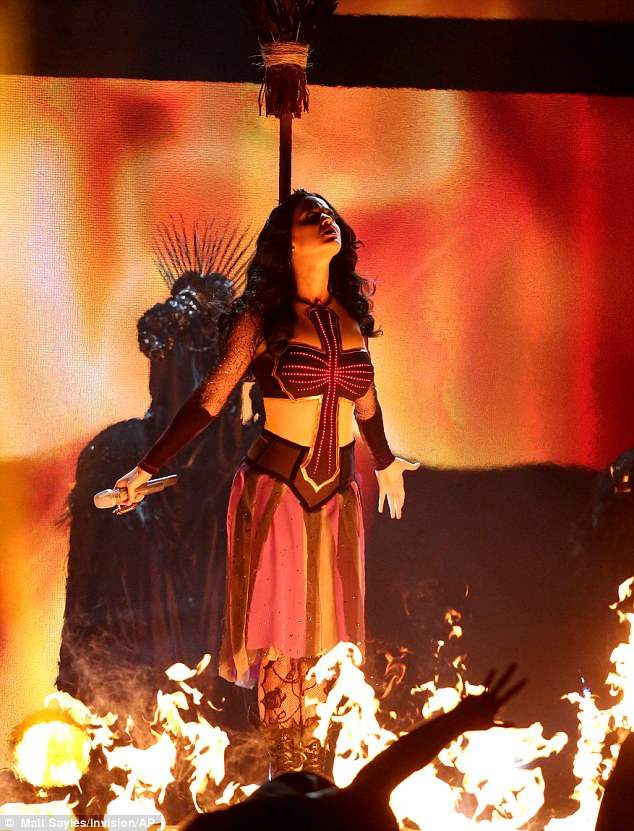 Dark magic: Katy's performance made us of pyrotechnics as she was tied to a broomstick on stage