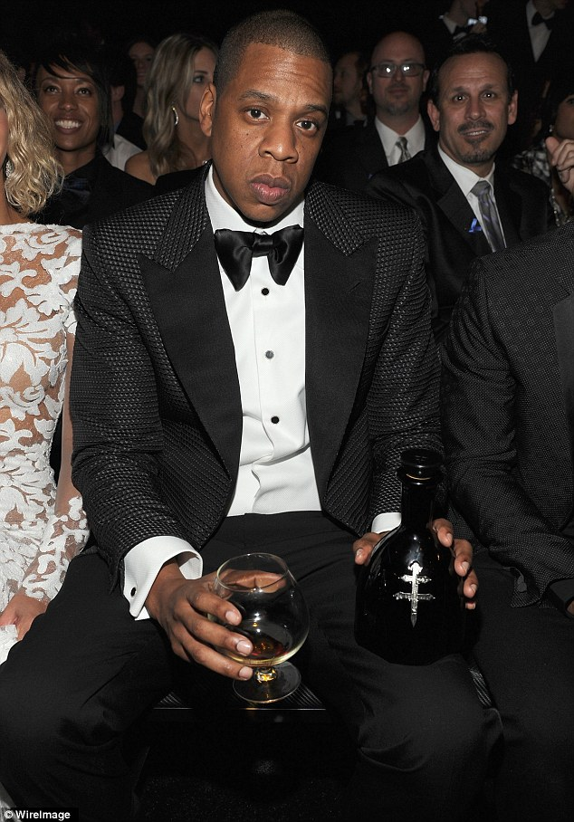 Enjoying himself: Jay was pictured with trademark bottle of cognac as he sat with wife Beyonce front row