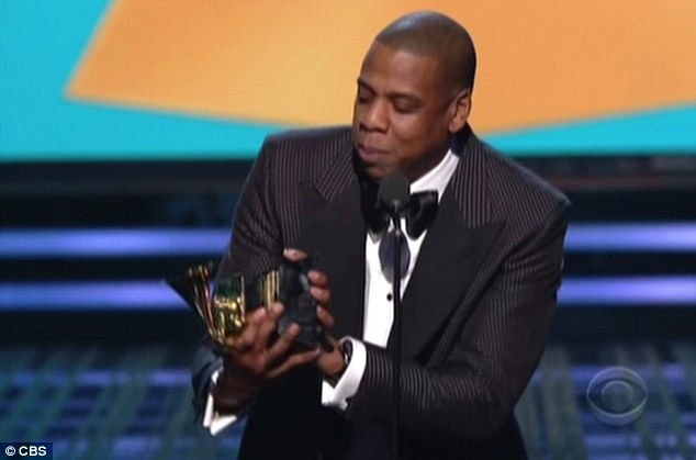 Multitasking: The moment Jay Z tilted his award, suggesting it could be a 'sippy cup' for daughter Blue