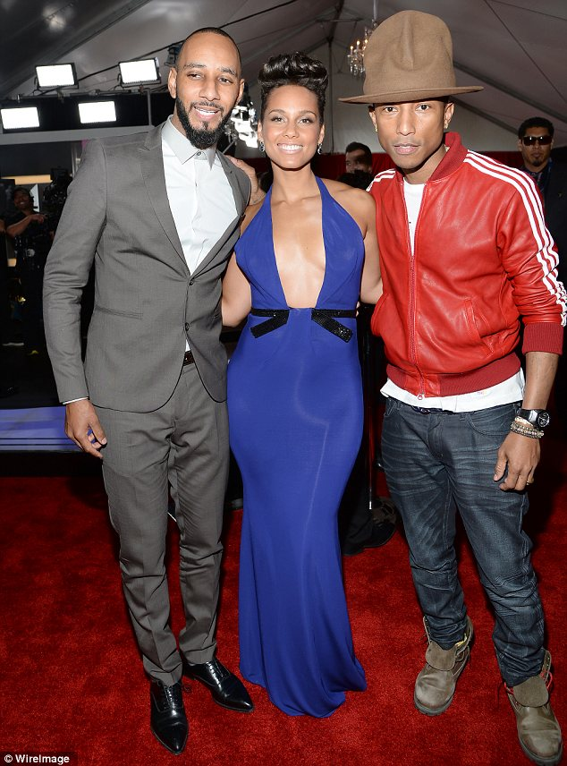 Busting out: Alicia posed with her husband Swizz Beatz and their pal Pharrell and looked in danger of showing off more than she bargained for