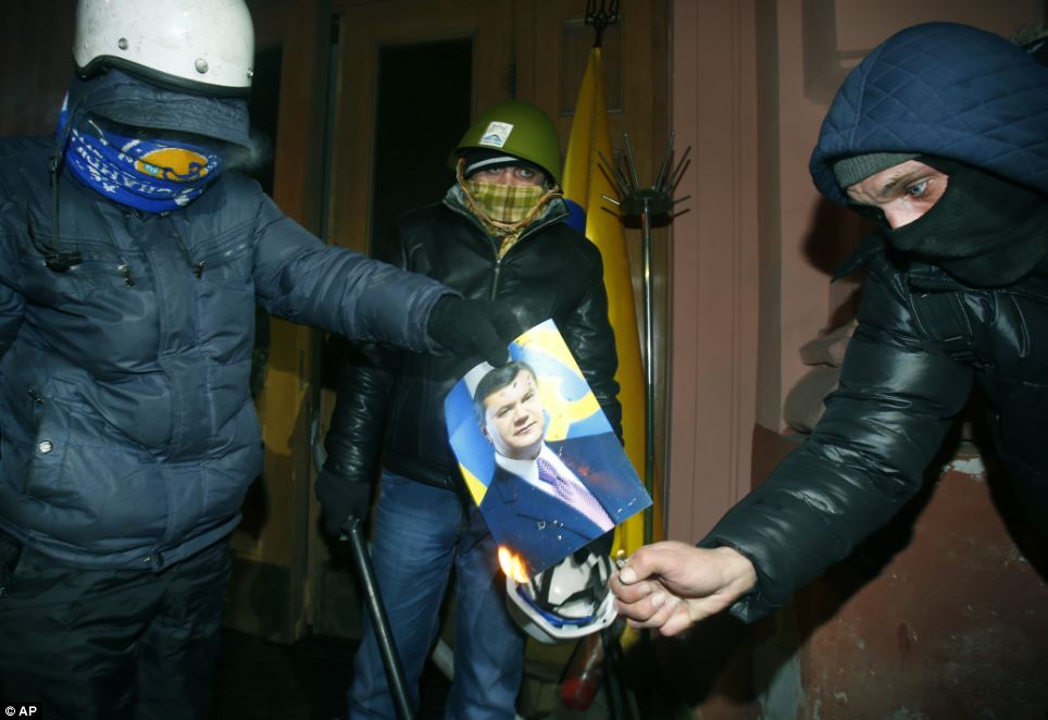 Violent: Hundreds of protestors burst into the building on Sunday night. They erected a number of barricades, before burning a portrait of President Viktor Yanukovych
