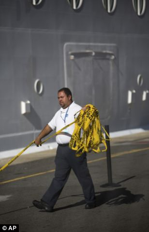 A West Indian Company employee removes a yellow caution barricade tape from around the ship