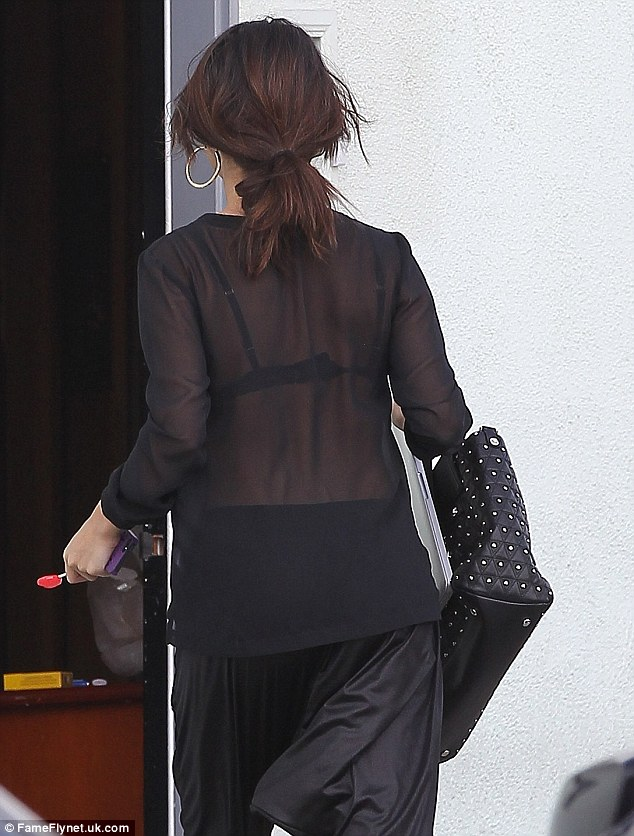 The bra is back! Selena later wore a black bra, sheer shirt, and harem trousers as she left her recording studio