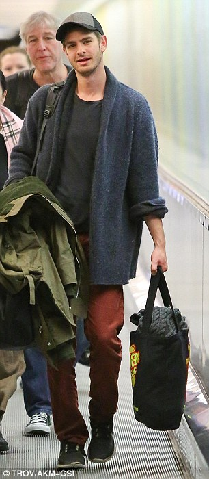 Flight suit: The Social Network star looked more Peter Parker than super hero, wearing a large unassuming knitted cardigan over a black T-shirt with a pair of rust coloured jeans and black Nike sneakers