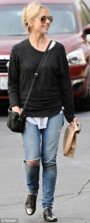 Trendy parents: Sarah wore a sheer black sweater, loose white blouse, distressed denim and oxford flats, as Liev wore a patterneds weater, grey zip-up, blue trousers and tan shoes