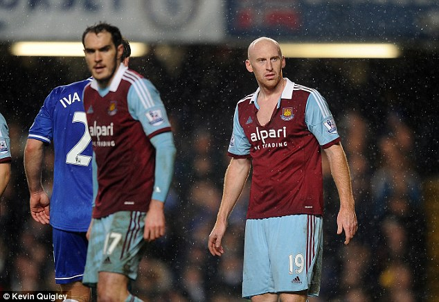 Physical battle: James Collins shows off his ripped shift after a coming together