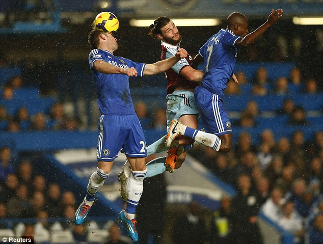 Clearance: Gary Cahill gets his head to the ball ahead of Carroll and Ramires