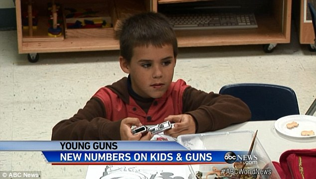 Not toys: This boy handles the gun like it is a toy after he begun rummaging around in a playbox at his school in Florida while filmed for the ABC News experiment