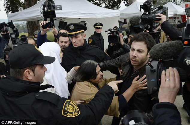 Fatima Khan (centre), the mother of British doctor Abbas Khan who died at 32 in a Syrian jail in disputed circumstances, is escorted away by United Nations security guards after trying to speak with members of the Syrian regime delegation in Geneva