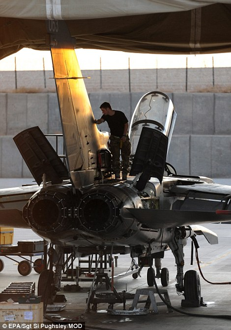 A crew member tends to his aircraft