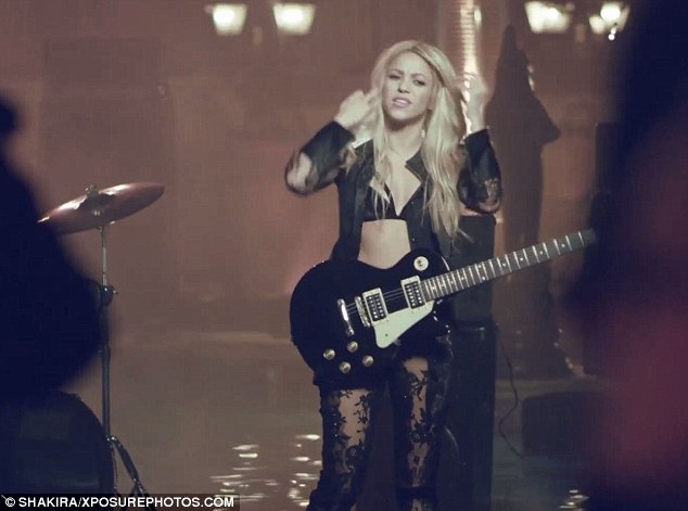 Sheer daring: The blonde singer plays an electric guitar while clad in a see-through open blouse, black bra and lacy leggings