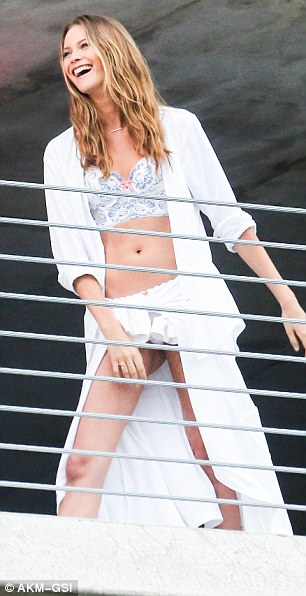 Having fun: Behati Prinsloo wore a blue-and-white lace bra and robe as she laughed for the camera