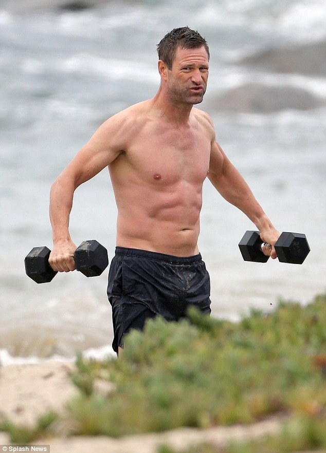 Looking good: Aaron Eckhart showed off his impressive physique as he worked out during a beachside photo shoot in Santa Monica, CA on Thursday
