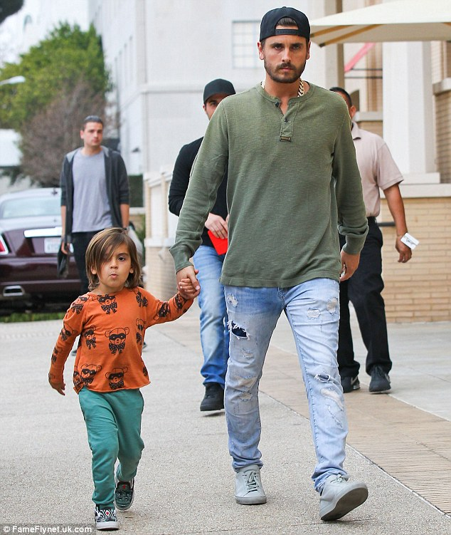 Walk the walk: Scott went for a casual grunge look for their outing while Mason was more colourful in a bright orange T-shirt and seagreen trousers