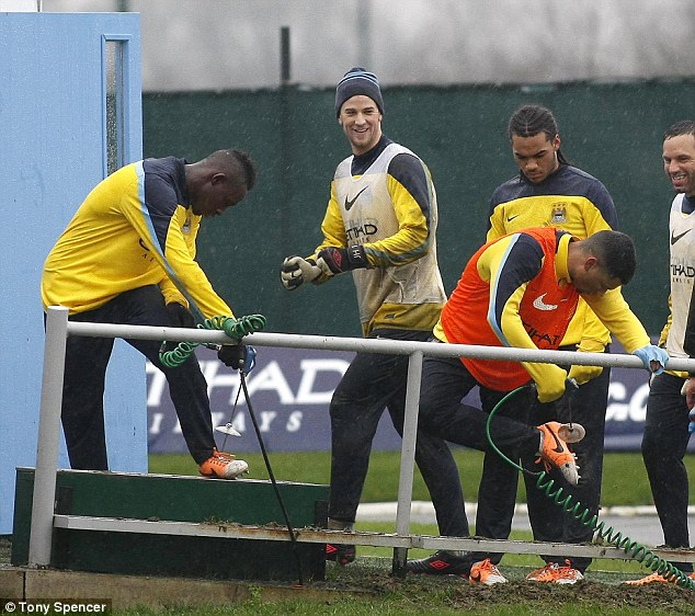 Preparation: City players wash off their muddy boots at training on deadline day. The team have a crunch clash with Chelsea on Monday