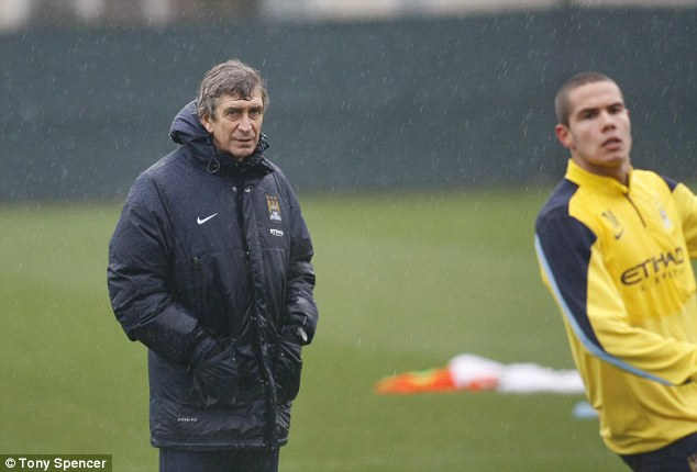 Rebuke: Manuel Pellegrini (left) - wet in training on Friday - is not interested in letting the defender go