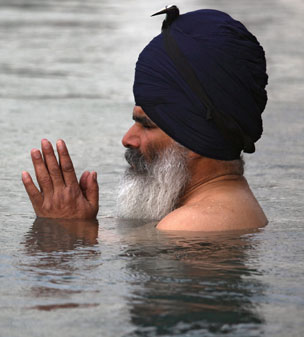 A Sikh devotee prays as he takes a holy dip in the sacred pond of the Golden Temple, in Amritsar, India