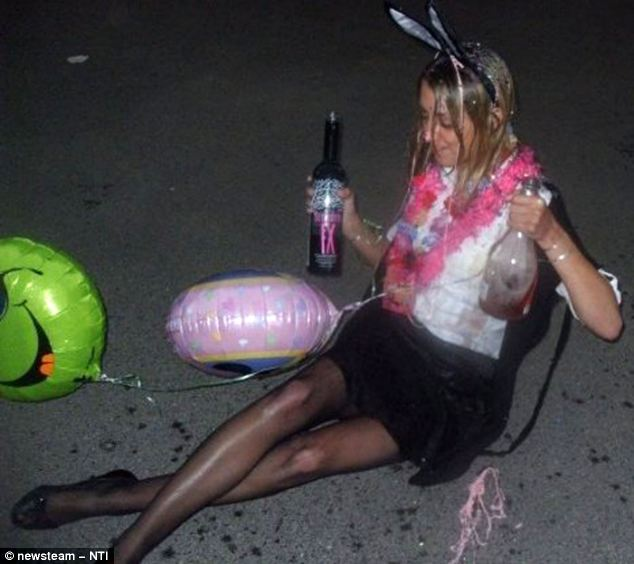 Floored: Celebrating her final exams at university, Miss Jones is pictured lying on the floor clutching bottles