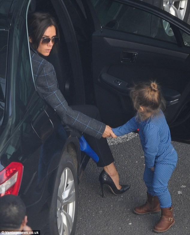 Mother's pride: Victoria Beckham travels light with her daughter Harper at Heathrow Airport