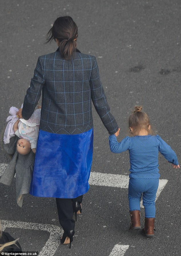 Smart: Victoria wore a smart grey and blue checked jacket with a royal blue dress over her black trousers