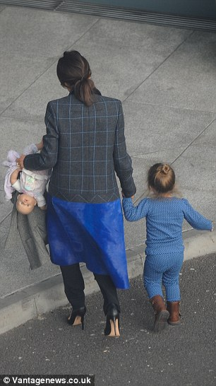 Harper was wearing a blue and white polka dot top and trousers with brown buckled leather boots