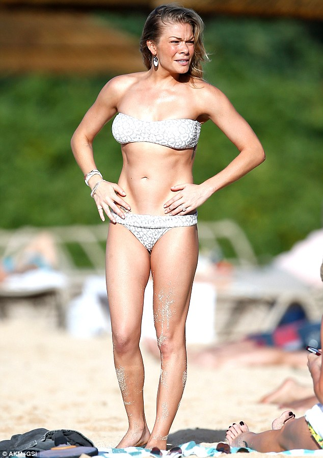 Bikini babe: LeAnn showed off her toned and tanned figure in a skimpy white two piece as she soaked up the sun at Monday