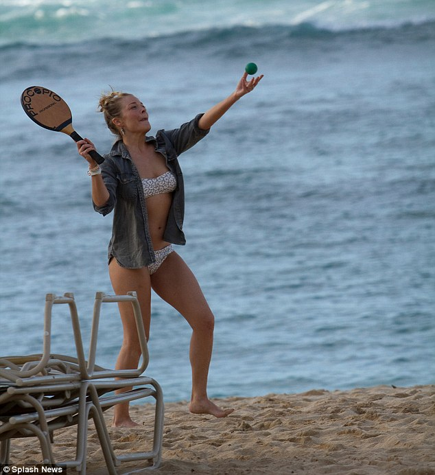 Smashing it: The star played a game of paddle tennis on the beach