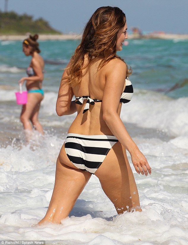 Wet and wild: Kelly shows off her curves as she strides into the surf