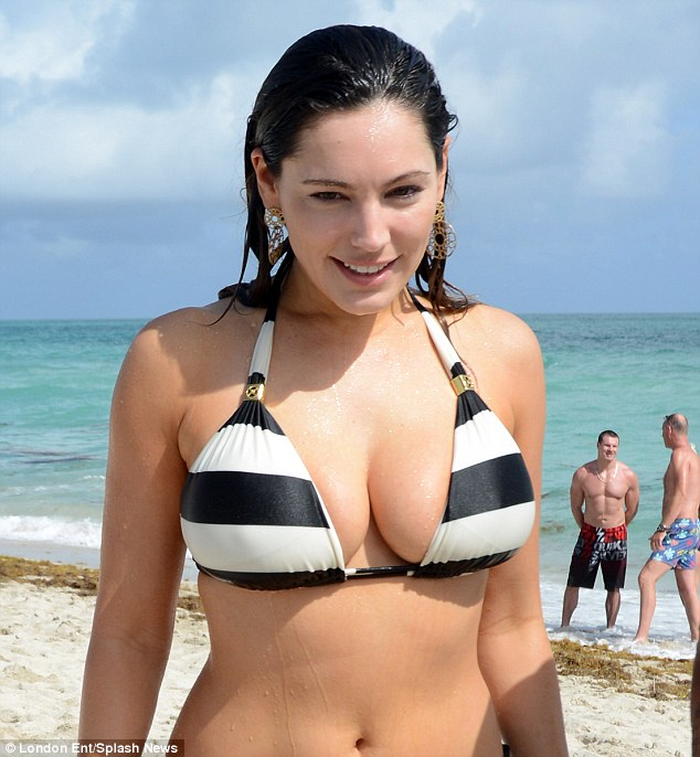 Flaunting it: Kelly's bikini top only just holds her ample assets