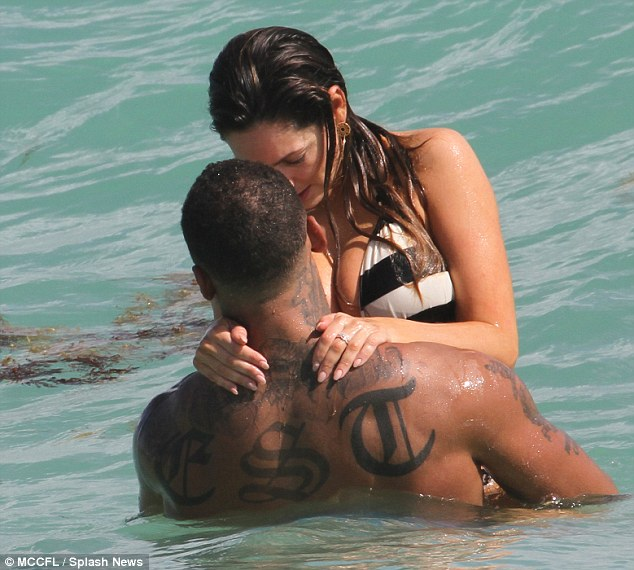 Stealing a kiss: The happy couple looked very much in love as they writhed around in the sea together