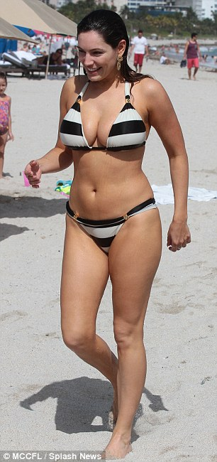 Smoking hot: The star turned heads as she walked along the beach in Miami