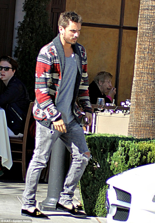 Hipster chic: Instead of a tailored suit, Scott wore a pair of grey distressed jeans with a grey T-shirt and a Southwesterned patterned knitted cardigan but still wore his signature slippers