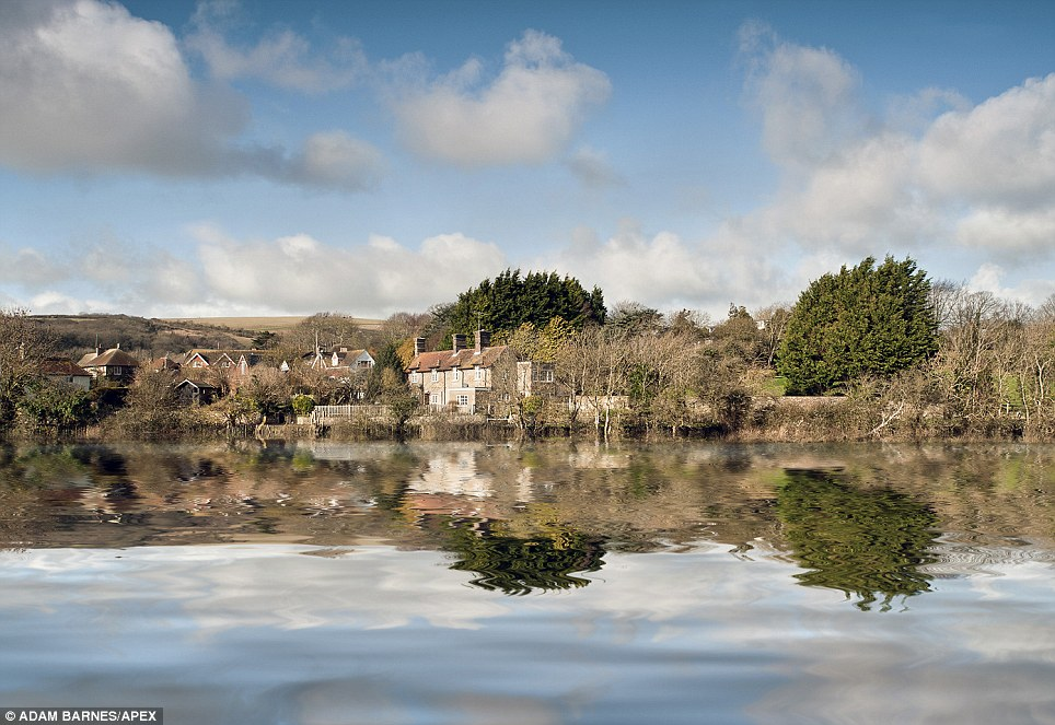 Beautiful reflection: A picture-postcard view of Alfriston in East Sussex - a village that has been surrounded by water since Christmas following relentless rain