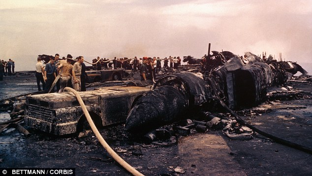 Charred Wreckage on deck of USS Forrestal which suffered heavy damage when fire engulfing the ship exploded bombs and rockets of aircraft off the coast of Vietnam in 1967