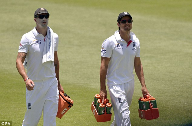 Distracted: Pietersen and Cook carrying the drinks off during a practise game in Australia this winter