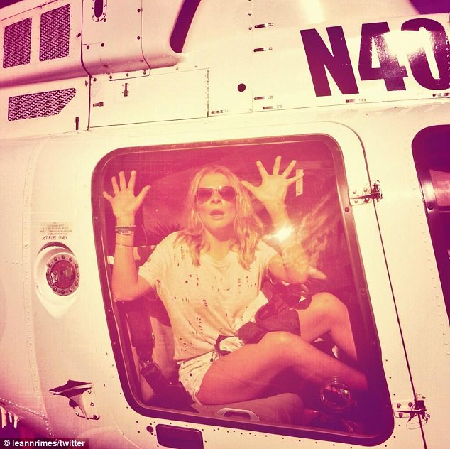 'Help me!' LeAnn goofed around in a helicopter while pretending to be trapped behind the glass window