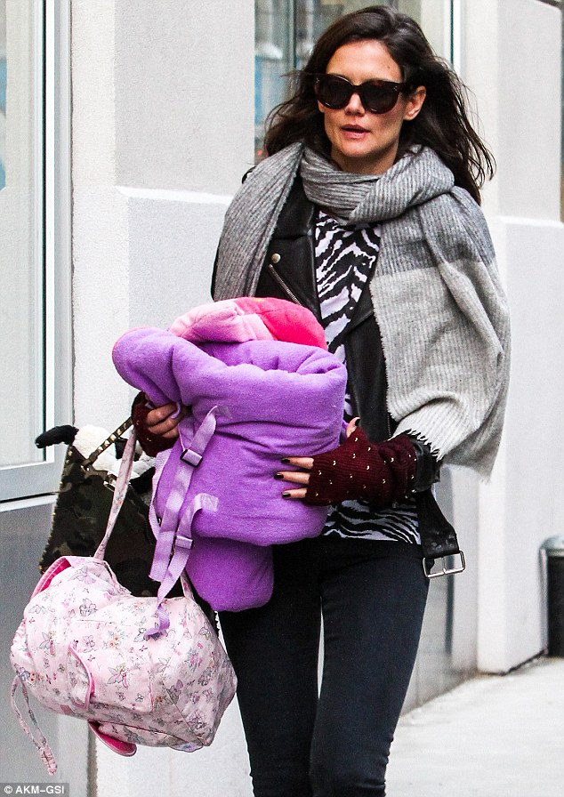 Doting mom: She looked quite conspicuous grasping onto her little one's patterned pink backpack and what appears to be a children's blanket and pillow