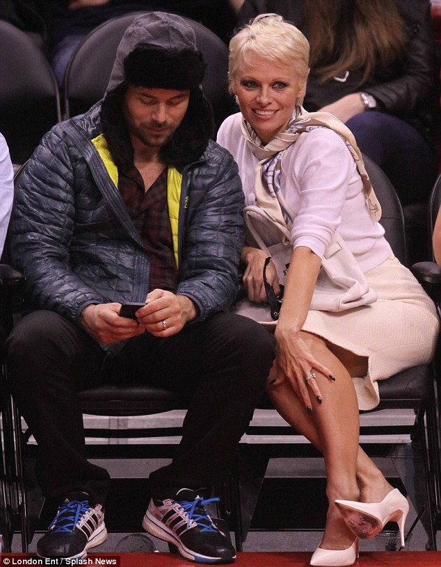 Something to tweet about? The blonde bombshell's husband checked his phone mid-game
